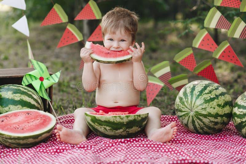 Glücklicher Kinderjunge, der draußen Wassermelone isst lizenzfreie stockfotos