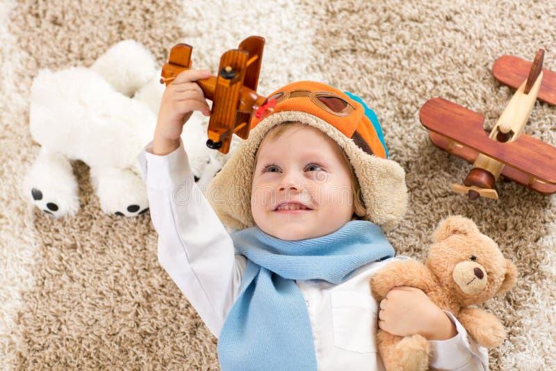 Glücklicher Kinderjunge, der mit Spielzeugflugzeug spielt stockfotografie