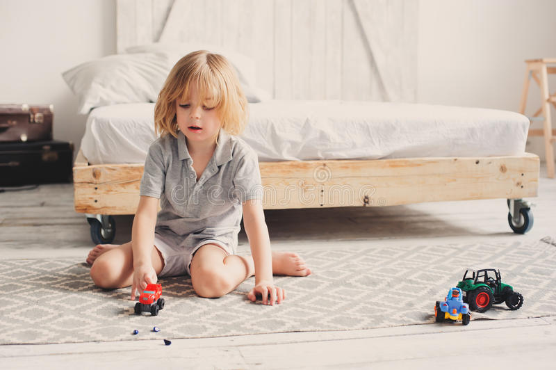 Glücklicher Kinderjunge, der zu Hause mit Spielzeugautos morgens spielt stockbild