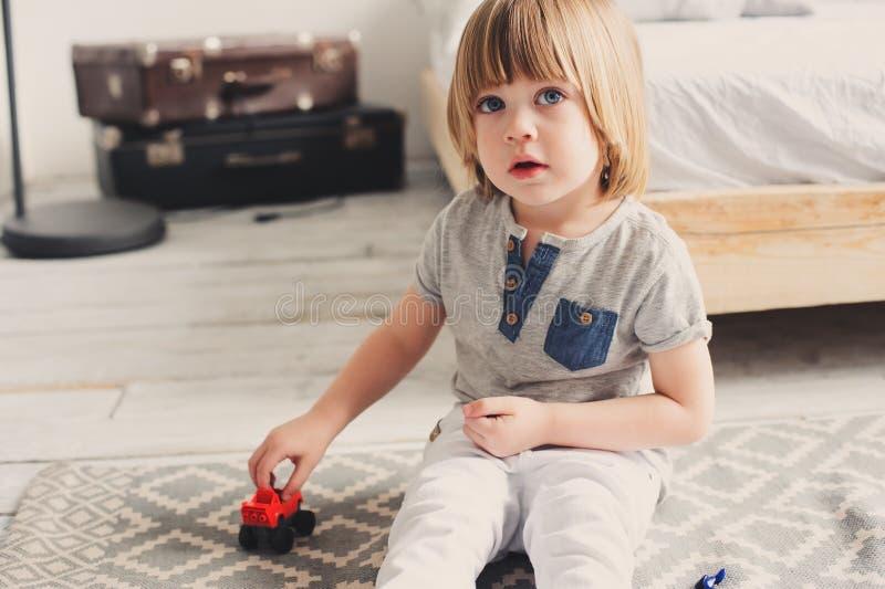 Glücklicher Kinderjunge, der zu Hause mit Spielzeugautos morgens spielt lizenzfreie stockfotos