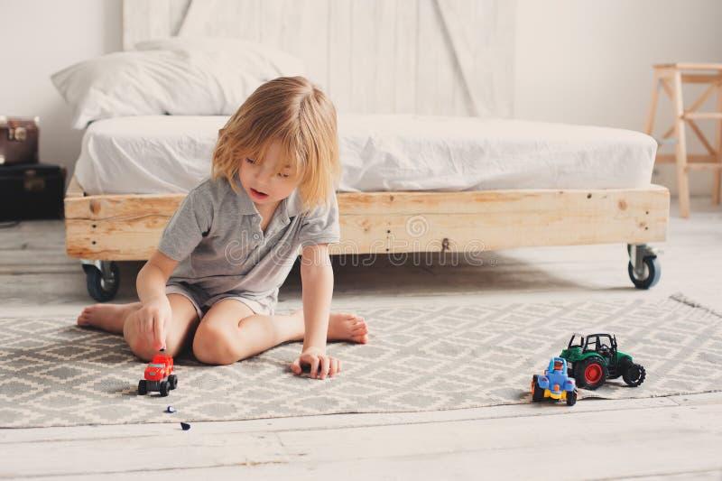 Glücklicher Kinderjunge, der zu Hause mit Spielzeugautos morgens spielt lizenzfreie stockfotografie