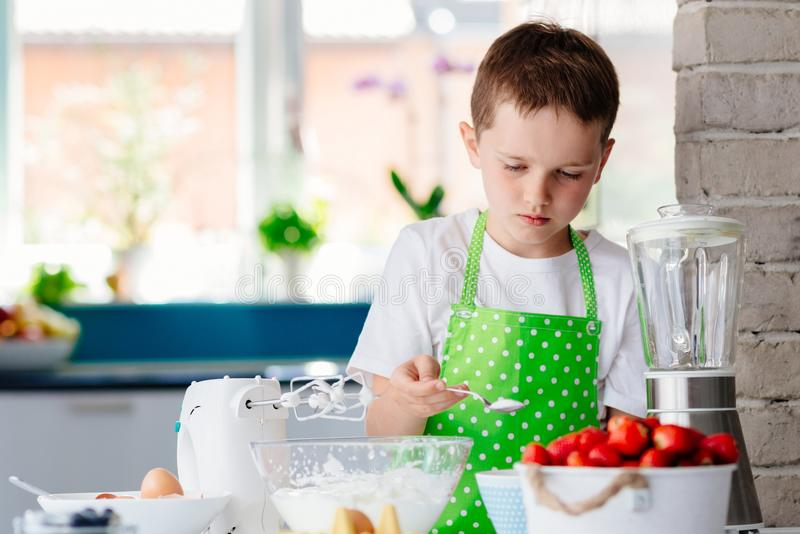 Glücklicher Kinderjunge, der Zucker Schüssel hinzufügt und einen Kuchen vorbereitet lizenzfreie stockbilder
