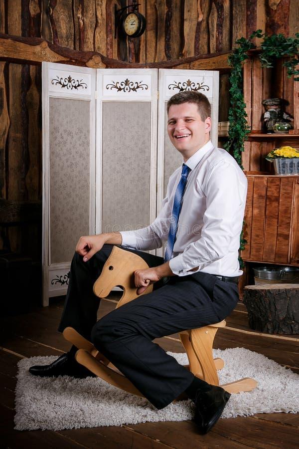 Glücklicher kindischer junger Mann fährt auf das hölzerne Spielzeugpferd lizenzfreies stockfoto