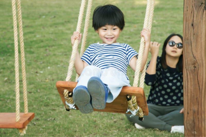 Glücklicher kleiner asiatischer Junge auf dem Schwingen- und Mutterdruck lizenzfreie stockfotos