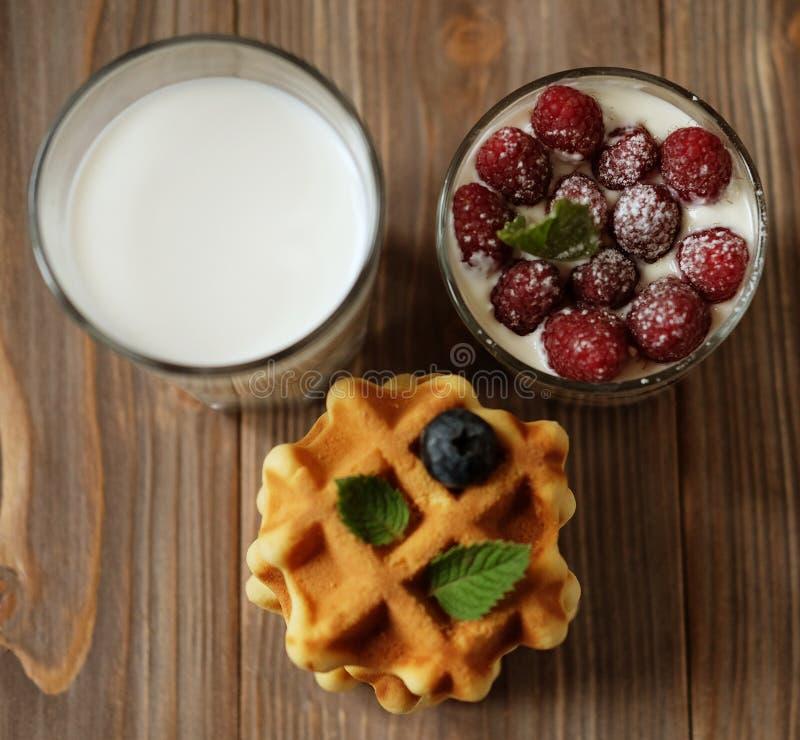 Glücklicher kleiner Becher des Frühstücks A mit Blaubeeren, einem Glas Milch und Granola mit Himbeeren lizenzfreie stockbilder