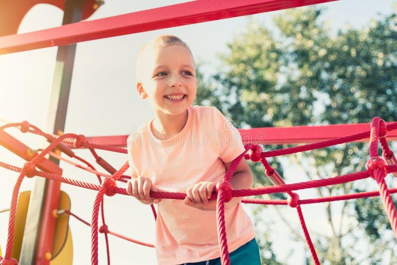 Glücklicher kleiner Junge auf kletterndem Rahmen des Kinderspielplatzes stockfoto