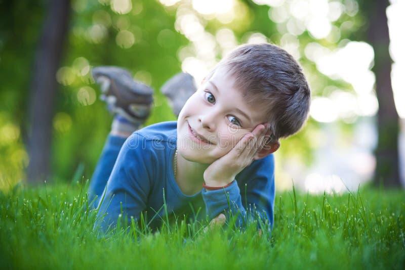 Glücklicher kleiner Junge, der auf das Gras legt lizenzfreies stockfoto
