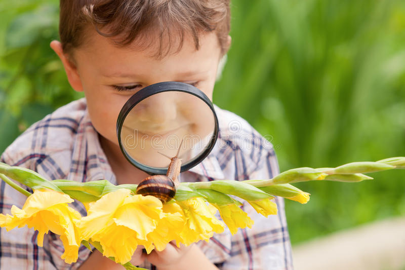 Glücklicher kleiner Junge, der im Park mit Schnecke zur Tageszeit spielt stockbilder