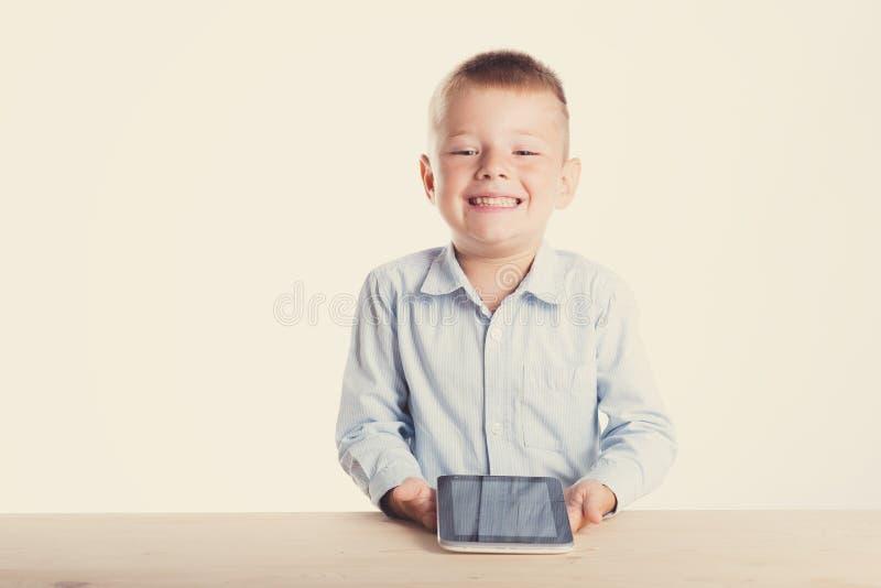 Glücklicher kleiner Junge in der Klage, die bei Tisch mit Tablettengerät sitzt Ein Portrait des Mädchenabschlusses oben Zurück zu stockbilder
