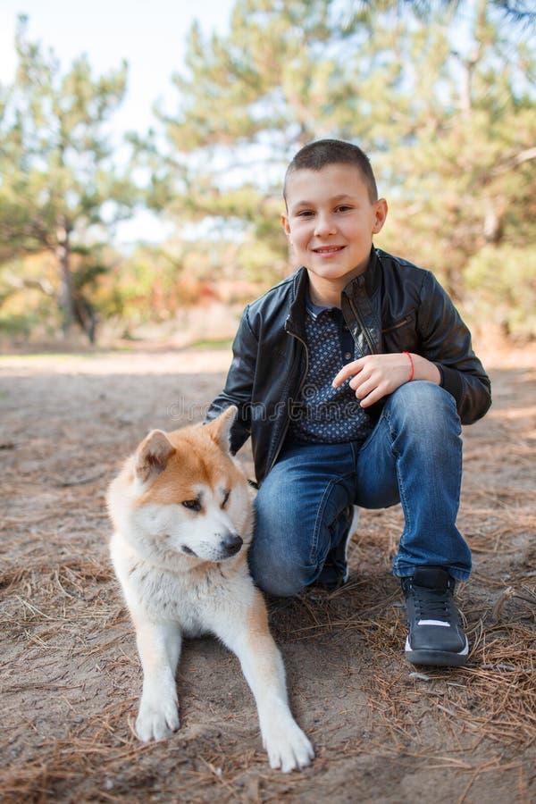 Glücklicher kleiner Junge, der mit Hund im Park geht Tierkonzept lizenzfreie stockbilder