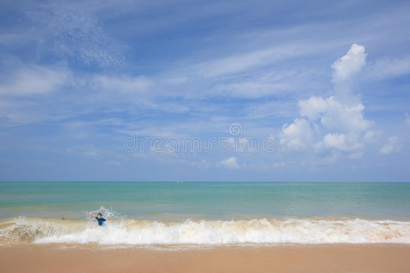 Glücklicher kleiner Junge, der in Ozean auf Ferien spielt und surft lizenzfreies stockfoto