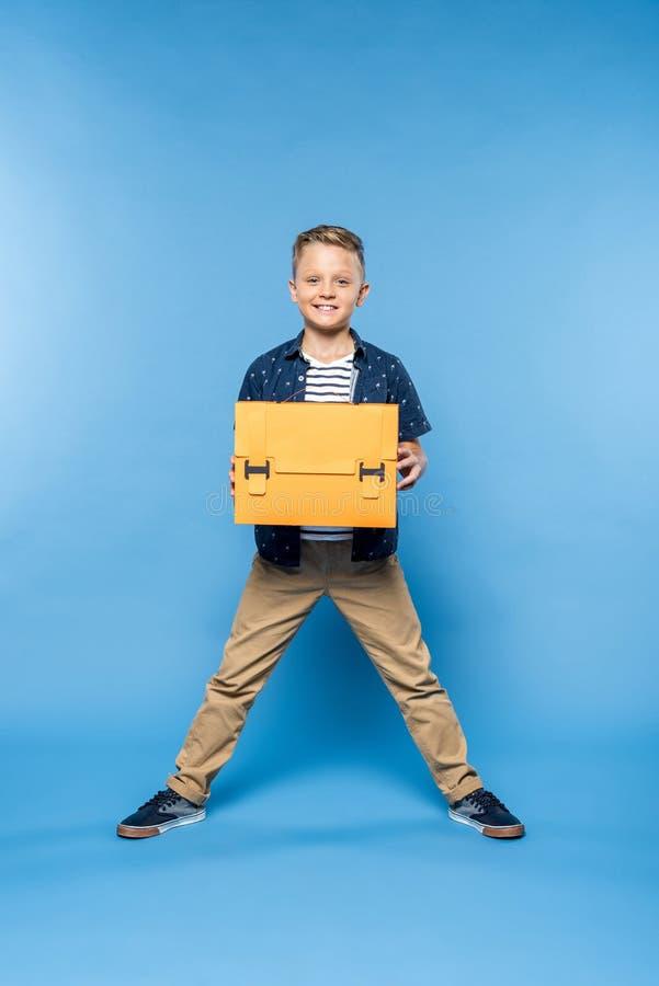 glücklicher kleiner Junge, der papercraft Aktenkoffer hält und an der Kamera lächelt lizenzfreie stockfotografie