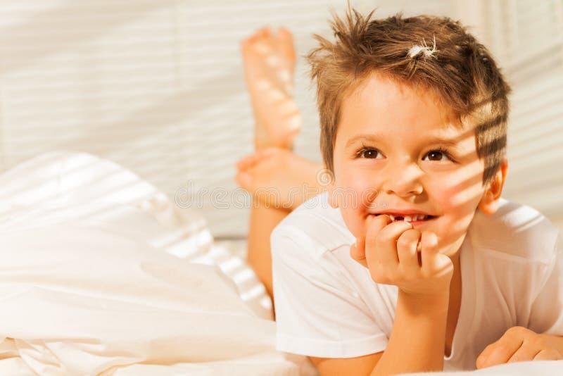 Glücklicher kleiner Junge, der in seinem Bett legt und träumt stockfotos