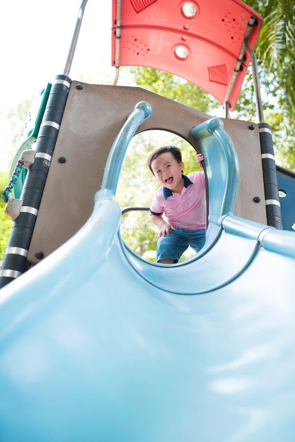 Glücklicher kleiner Junge, der Spaß am Spielplatz im Sommer hat stockbilder