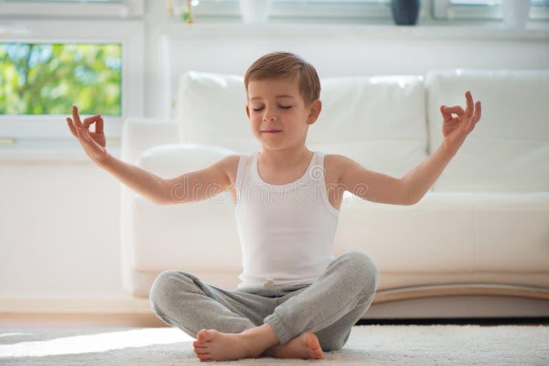Glücklicher kleiner Junge, der zu Hause trainiert stockbilder