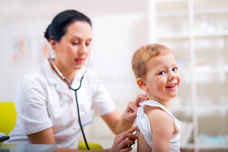 Glücklicher kleiner Junge am Doktor für eine Überprüfung lizenzfreie stockbilder