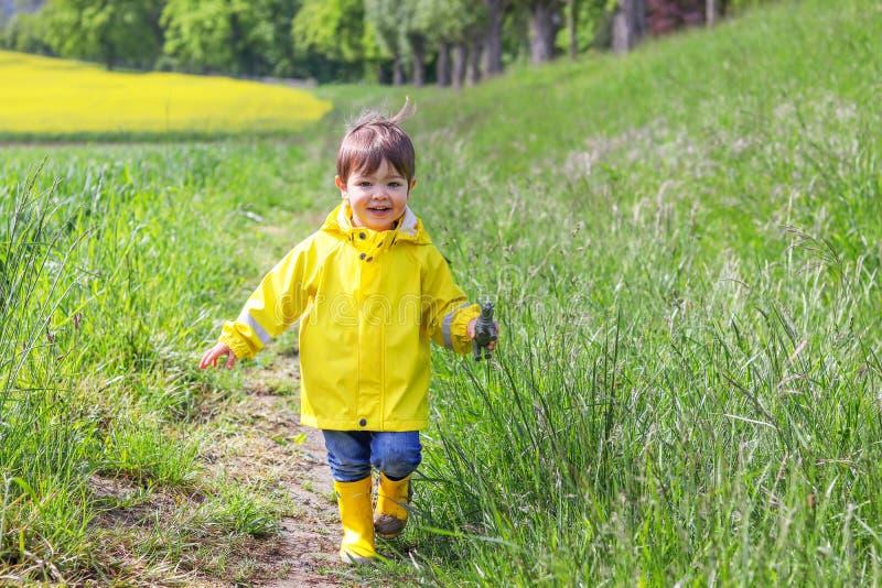 Glücklicher kleiner Junge im gelben Regenmantel und schlammigen Gummiin den stiefeln, die auf Schotterweg durch grünes Gras nahe  lizenzfreie stockfotografie