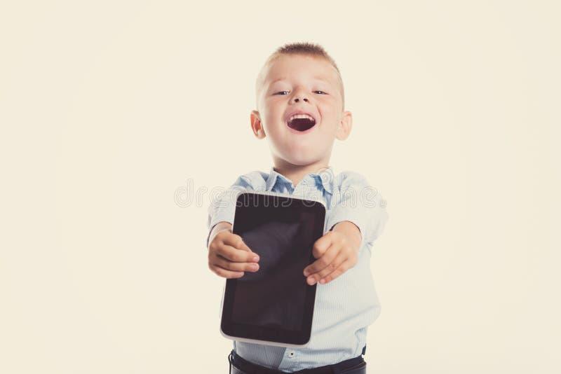 Glücklicher kleiner Junge im Klagengriff-Tablettengerät Ein Portrait des Mädchenabschlusses oben Zurück zu Schule Stilvoller Mann stockfoto