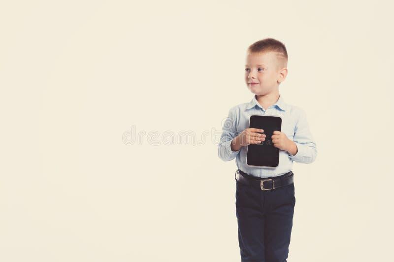 Glücklicher kleiner Junge im Klagengriff-Tablettengerät Ein Portrait des Mädchenabschlusses oben Zurück zu Schule Stilvoller Mann lizenzfreie stockfotos