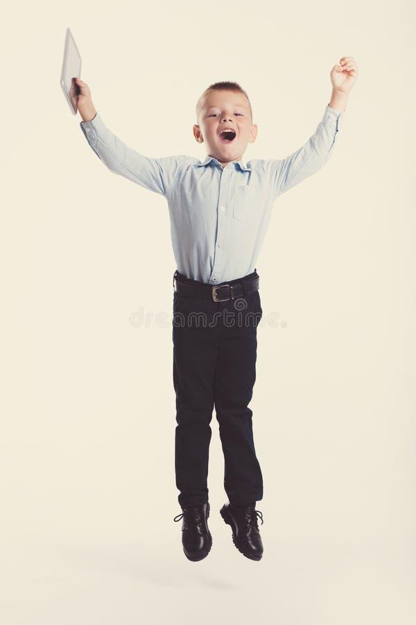 Glücklicher kleiner Junge im Klagensprungs- und Grifftablettengerät Ein Portrait des Mädchenabschlusses oben Zurück zu Schule Sti stockbild