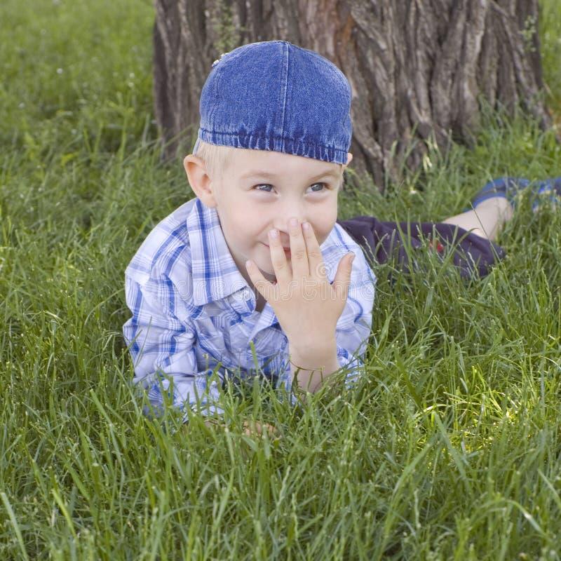 Glücklicher kleiner Junge ist auf einem Rasen stockfotografie