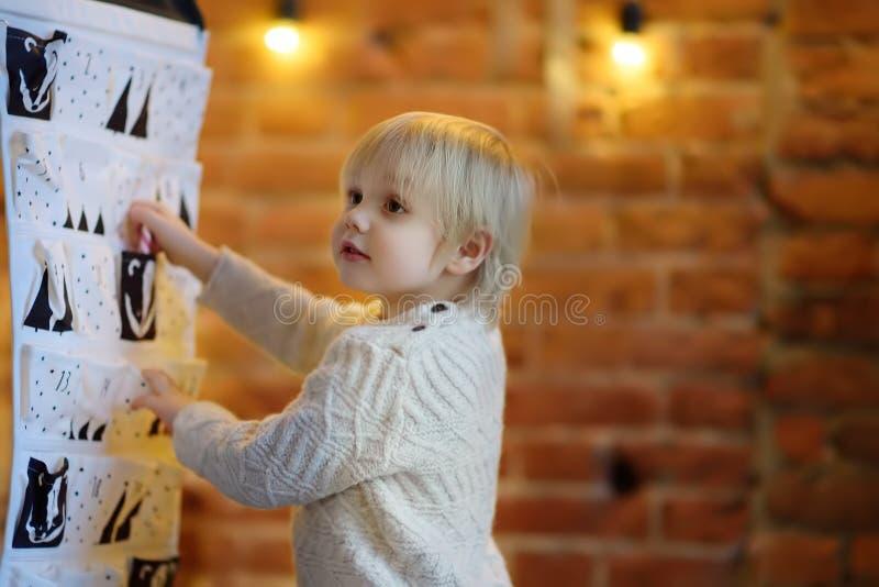 Glücklicher kleiner Junge nimmt Bonbon vom Einführungskalender auf Weihnachtsabend lizenzfreie stockbilder