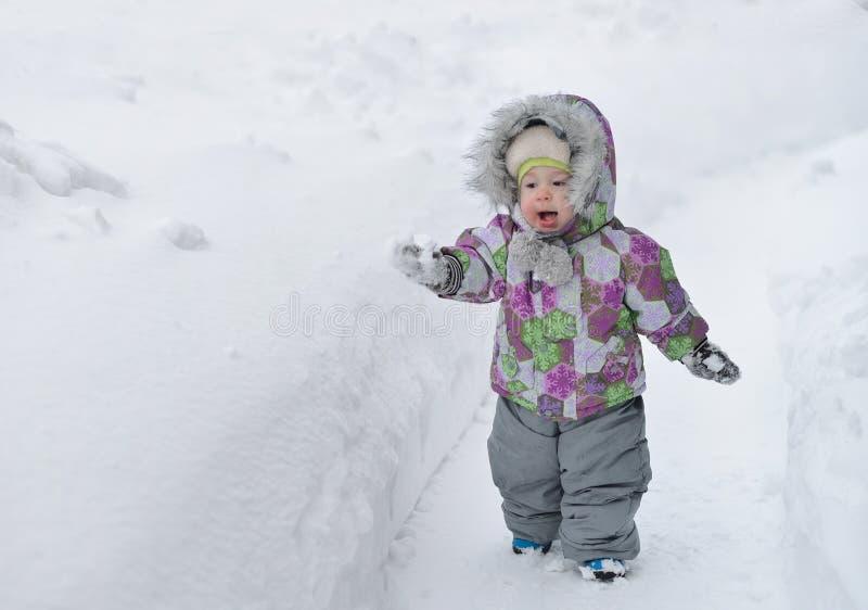 Glücklicher kleiner Junge spielt mit Schnee auf winer Hintergrund lizenzfreie stockfotografie