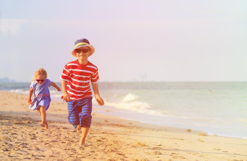 Glücklicher kleiner Junge und das Mädchen, die auf Sand läuft, setzen auf den Strand lizenzfreie stockfotos
