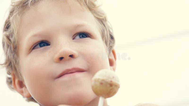 Glücklicher kleiner Vorschuljunge mit Süßigkeit lollypop am Sommerstrand, draußen stockfoto