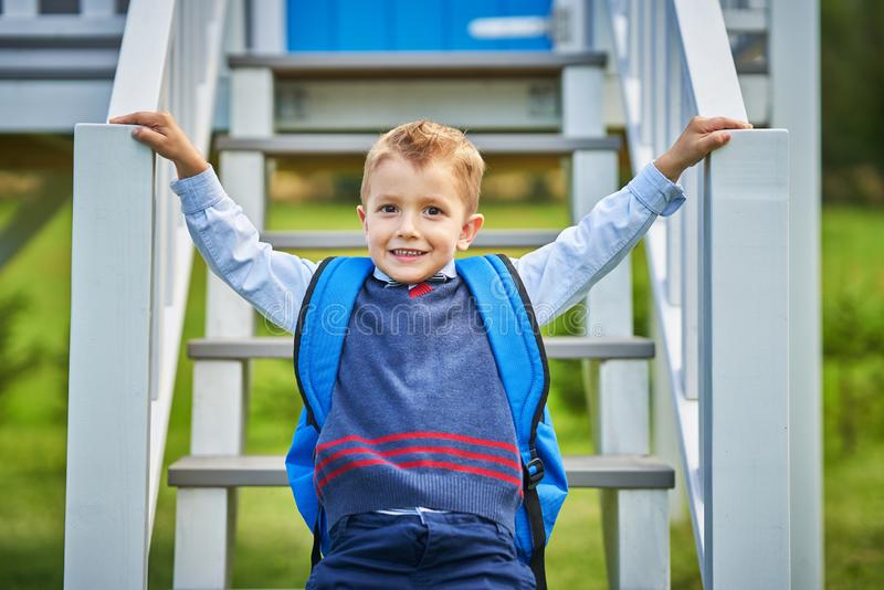 Glücklicher kleiner Vorschulkinderjunge mit dem Rucksack, der draußen aufwirft lizenzfreie stockfotografie