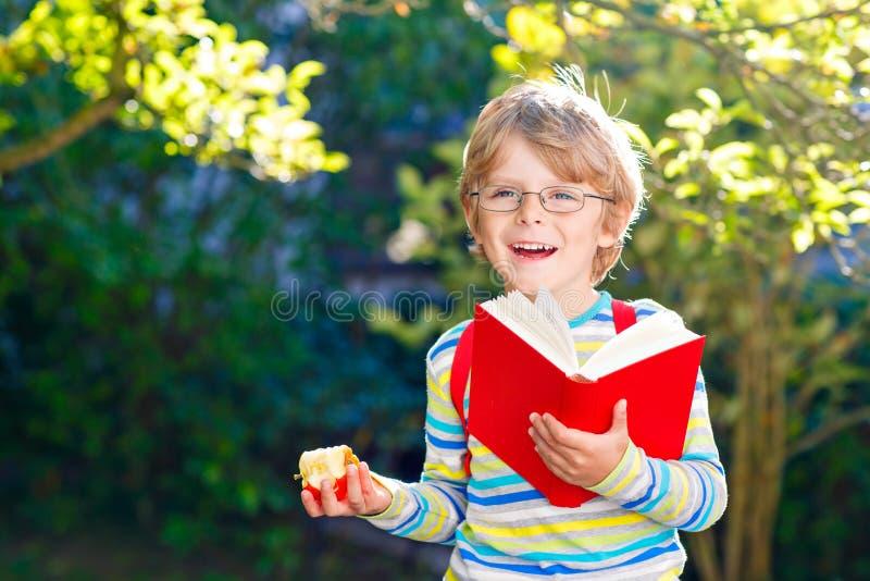 Glücklicher kleiner Vorschulkinderjunge mit Gläsern, Büchern, Apfel und Rucksack an seinem ersten Tag zur Schule oder zur Kindert stockfoto