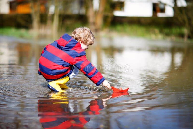 Glücklicher Kleinkindjunge in den gelben Regenstiefeln, die mit Papierschiffsboot durch enorme Pfütze am Frühlings- oder Herbstta lizenzfreie stockfotos