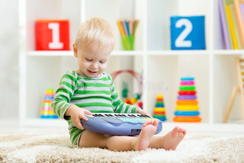 Glücklicher Kleinkindjunge, der Klavierspielzeug spielt stockfoto