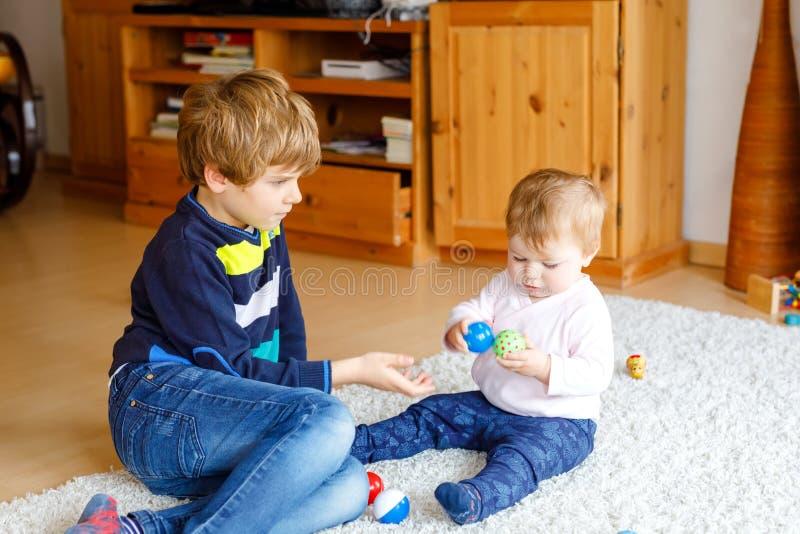Glücklicher Kleinkindjunge mit nettem kleinem Baby, nette Schwester geschwister Bruder und Baby, die zusammen spielen Älteres Kin stockfotografie