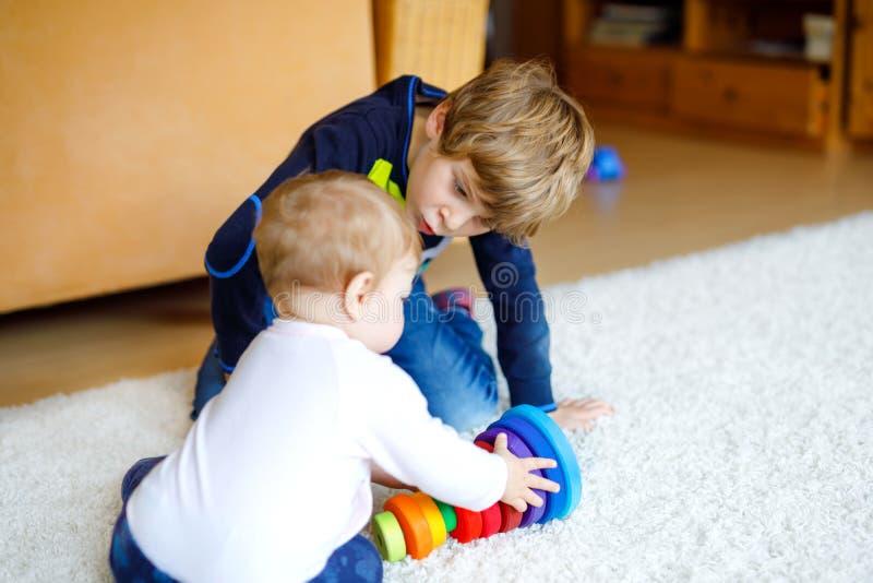 Glücklicher Kleinkindjunge mit nettem kleinem Baby, nette Schwester geschwister Bruder und Baby, die zusammen spielen Älteres Kin stockbild