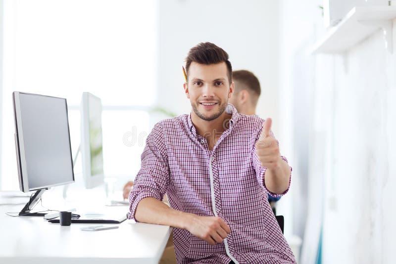 Glücklicher kreativer Mann mit Computer im Büro lizenzfreie stockfotografie