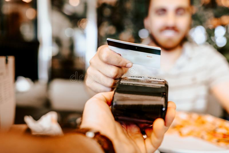 Glücklicher Kunde, der für das Mittagessen unter Verwendung der neuen, modernen kontaktlosen Technologie mit Kreditkarte zahlt stockfotografie