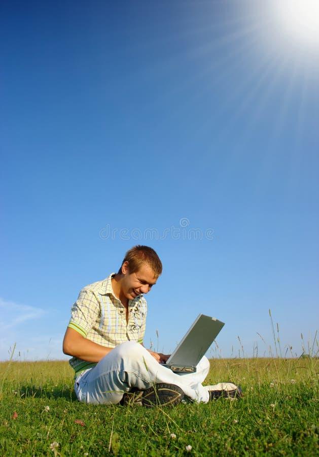 Glücklicher Kursteilnehmer, der mit Laptop auf grüner Wiese arbeitet lizenzfreies stockfoto