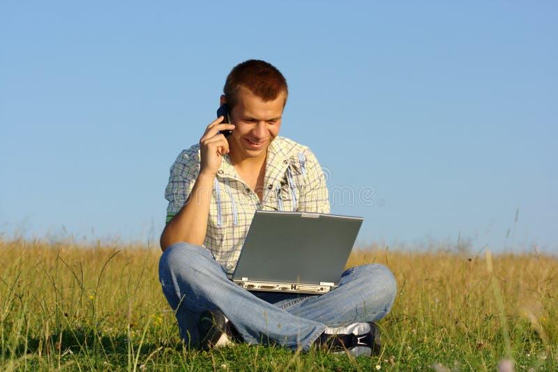 Glücklicher Kursteilnehmer, der mit Laptop auf grüner Wiese arbeitet lizenzfreies stockbild