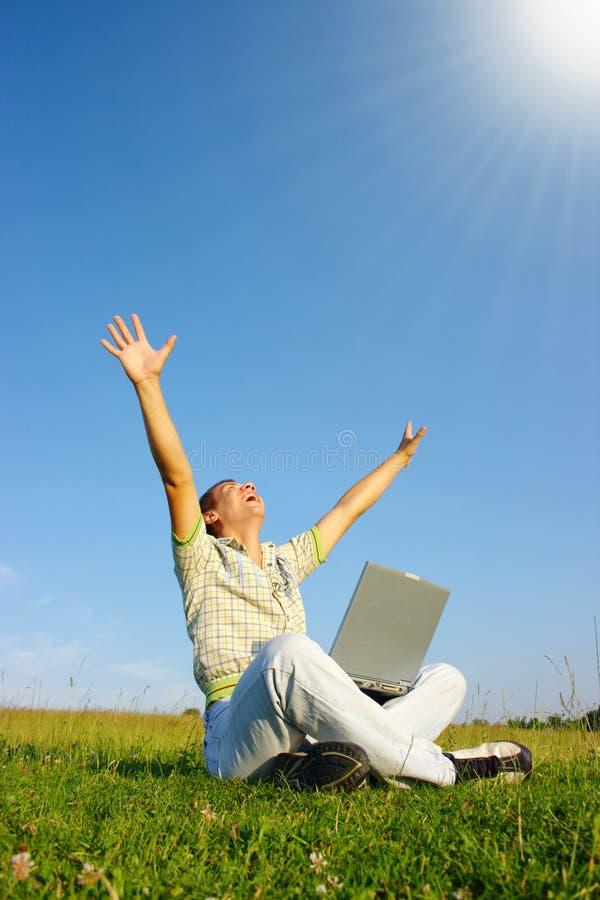 Glücklicher Kursteilnehmer mit Laptop auf grüner Wiese lizenzfreies stockfoto