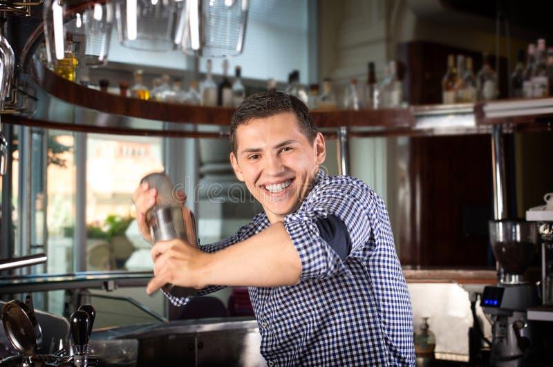 Glücklicher lächelnder Barmixer, der ein Cocktail im Stahlschüttel-apparat rüttelt stockfotos