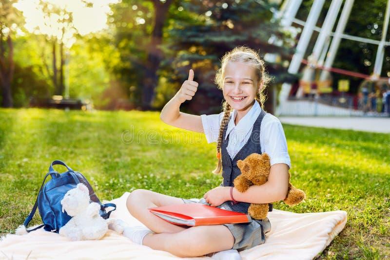 Glücklicher lächelnder darstellender Daumen des Schulmädchenstudenten sitzt oben auf einer Decke im Park an einem sonnigen Tag de lizenzfreie stockfotos