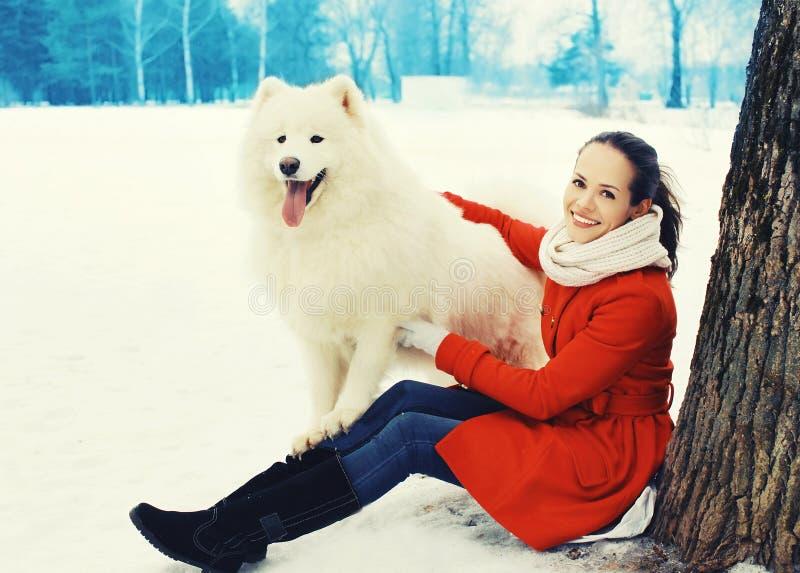 Glücklicher lächelnder Eigentümer der jungen Frau mit weißem Samoyedhund auf Schnee im Winter lizenzfreie stockfotos