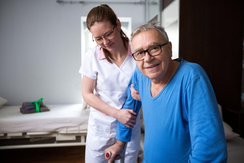 Glücklicher lächelnder erfüllter älterer Mann am Pflegeheim stockfoto