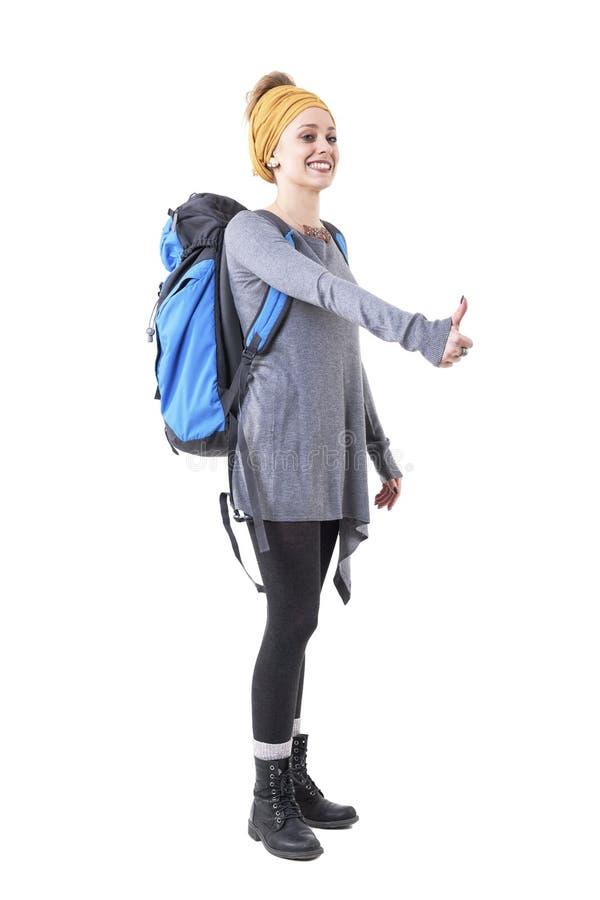 Glücklicher lächelnder Forscher der jungen Frau mit Rucksack per Anhalter fahrend mit Fingergeste lizenzfreies stockbild