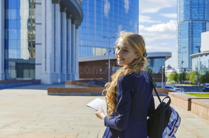 Glücklicher lächelnder freiberuflich tätiger Student, der auf Stadtstraße geht lizenzfreie stockbilder