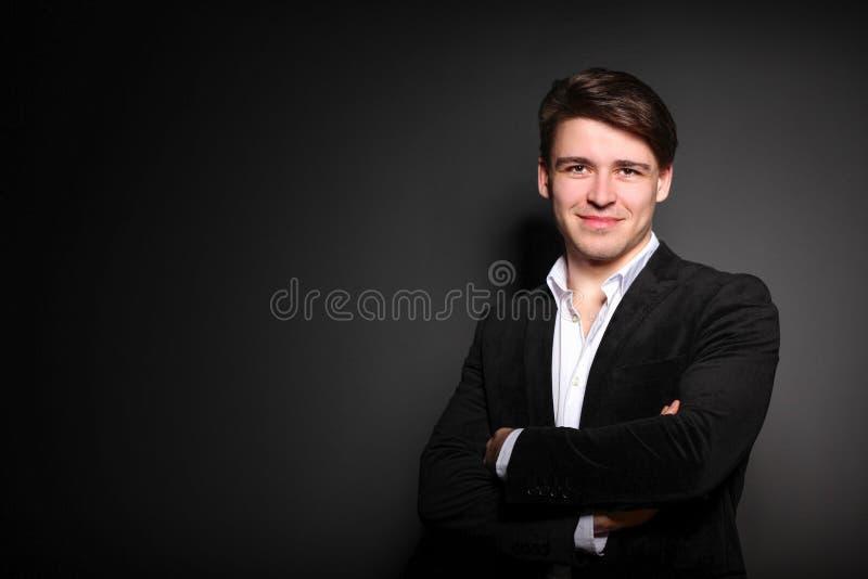Glücklicher lächelnder Geschäftsmann in der Klage, die mit den cossed Armen steht lizenzfreie stockfotografie