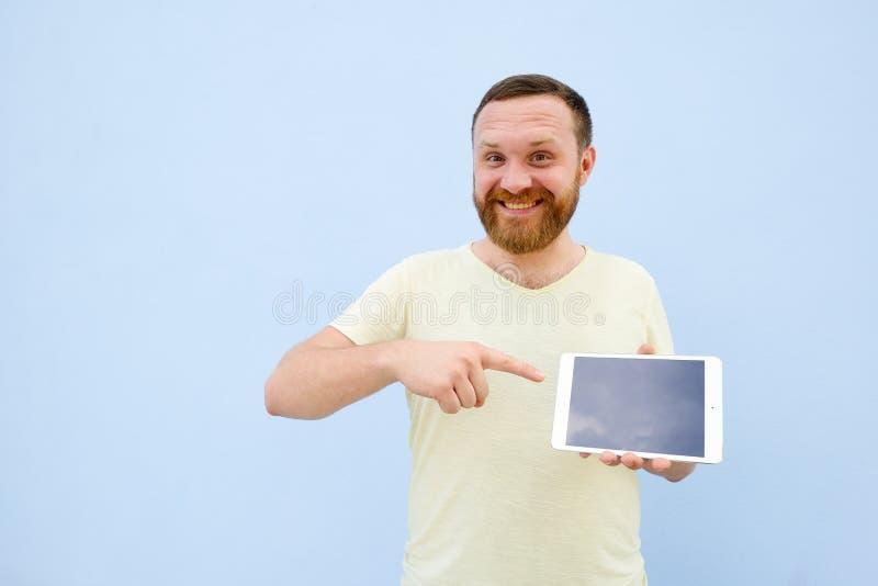 Glücklicher lächelnder hübscher junger Mann mit einem Bart, der etwas auf einer Tablette auf einem blauen Hintergrund, hell und h lizenzfreie stockfotografie