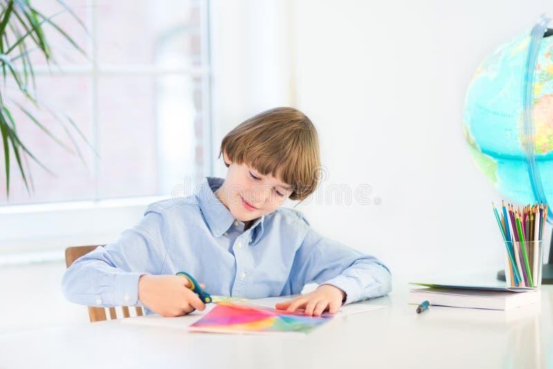 Glücklicher lächelnder Junge, der buntes Papier mit Scheren schneidet stockbild
