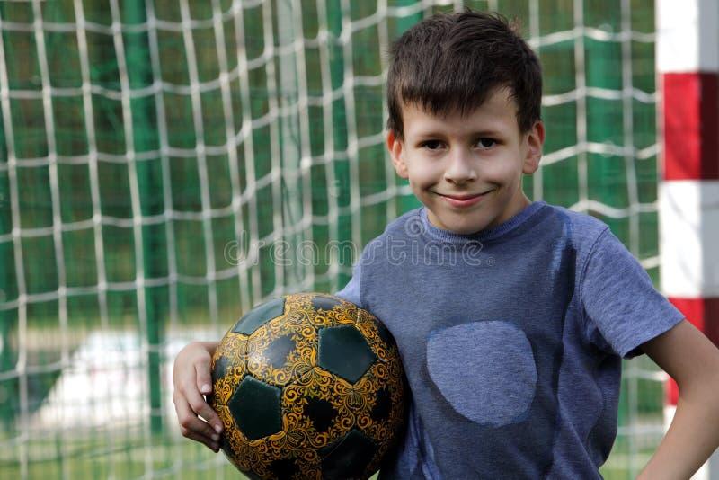 Glücklicher lächelnder Junge mit Fußballball stockbilder